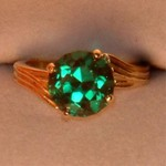 This cocktail ring features a huge 10mm 3.21ct lab created emerald set in 14K yellow gold.