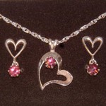 This Heart shaped pendant and earring set made from sterling silver feature a matched set of amazingly brilliant Rhodolite Garnets.